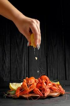 Aragosta con limone lime e aneto verde su sfondo nero, mano di donna con limone, lo chef spreme il succo di limone