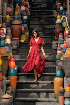 Ceramica locale. bella ragazza che china la testa mentre guarda le scale, vasi di argilla colorati in vendita