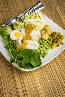 Vermicelli di riso locali e salsa al curry con verdura (kanom jeen nam ya)