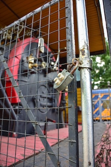 Il lucchetto sul reticolo metallico, la porta a traliccio chiusa, il lucchetto del primo piano