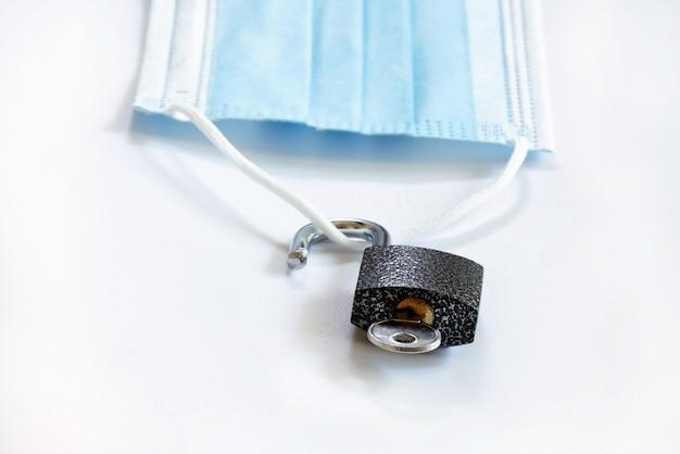 Il blocco e la pandemia sono sopra la maschera medica che giace sulla superficie bianca con un lucchetto aperto con una chiave