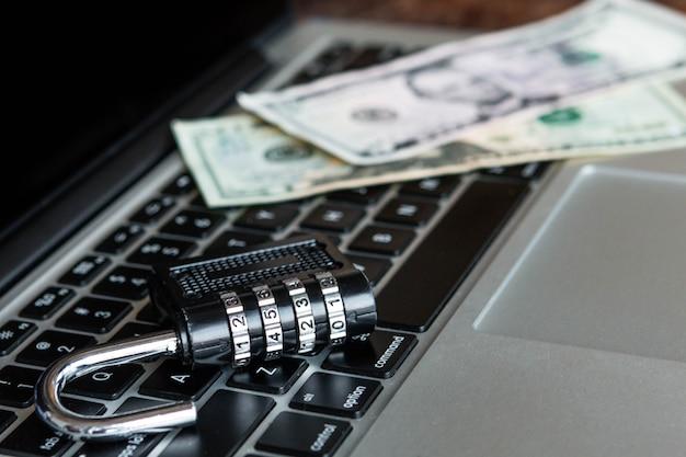 Armadietto e dollari su un computer portatile. concetto online di sicurezza
