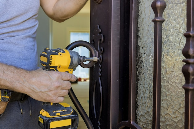 La mano del fabbro tiene il cacciavite nell'installazione della nuova serratura della porta di casa