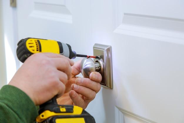 Il fabbro installa la nuova serratura fittizia della porta in casa.