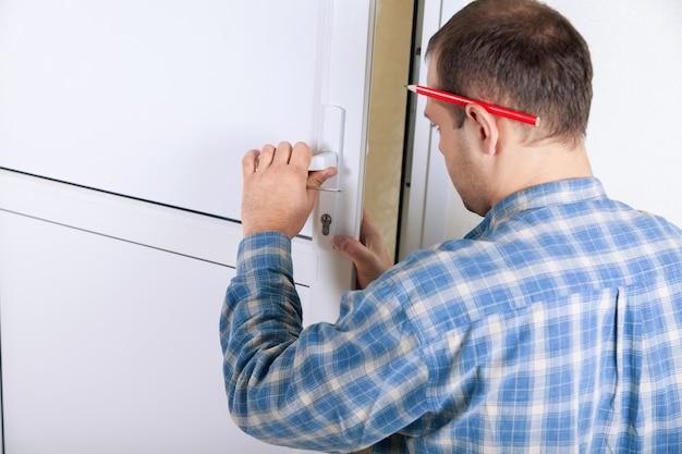 Fabbro che installa una serratura su una nuova porta bianca