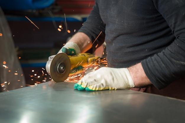 Fabbro in abiti speciali e occhiali di protezione lavora nella produzione. lavorazione del metallo con smerigliatrice angolare. scintille nella lavorazione dei metalli.