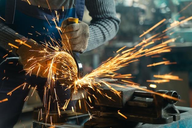 Fabbro in abiti speciali e occhiali di protezione lavora in produzione. lavorazione del metallo con smerigliatrice angolare. scintille nella lavorazione dei metalli.
