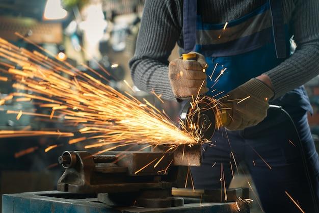Fabbro in abiti speciali e occhiali di protezione lavora in produzione. lavorazione del metallo con smerigliatrice angolare