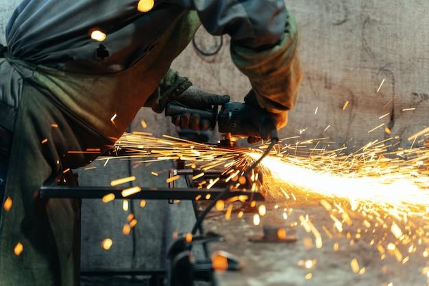 Il fabbro in abiti speciali e occhiali lavora nella lavorazione dei metalli di produzione con smerigliatrice angolare
