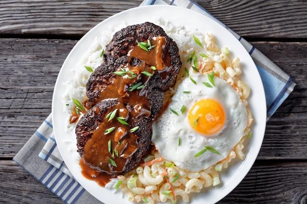 Loco moco di riso bianco, condita con un tortino di hamburger, un uovo fritto, sugo marrone e insalata di maccheroni servita su un piatto bianco su un tavolo in legno rustico, vista dall'alto, flatlay