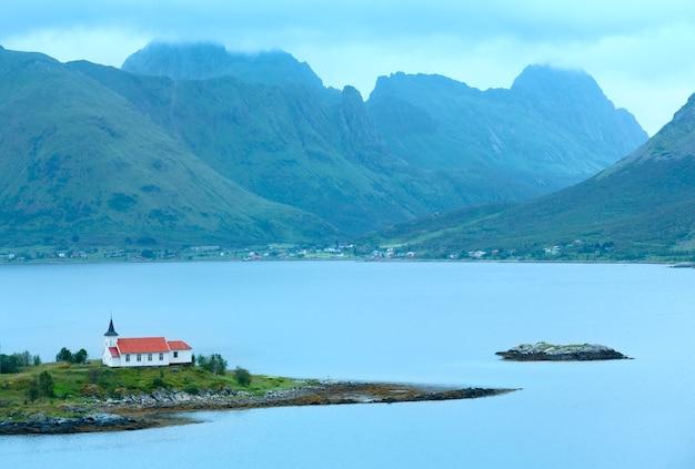 Vista nuvolosa di estate di lofoten con la chiesa sull'isola.
