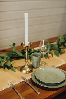 Il tavolo da pranzo loft è decorato con fiori, candele ed erbe aromatiche. messa a fuoco selettiva morbida.