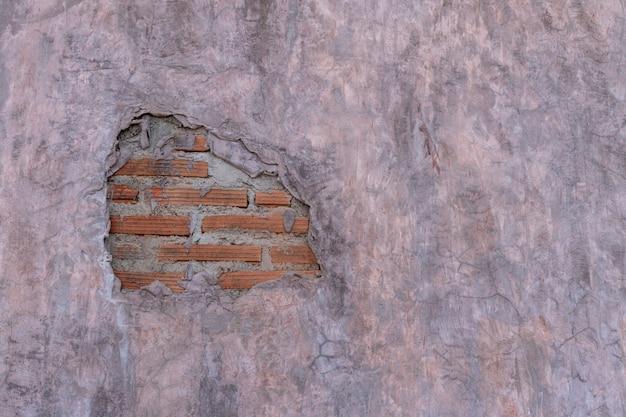 Muro di cemento in stile loft con crepa e mattoni arancioni