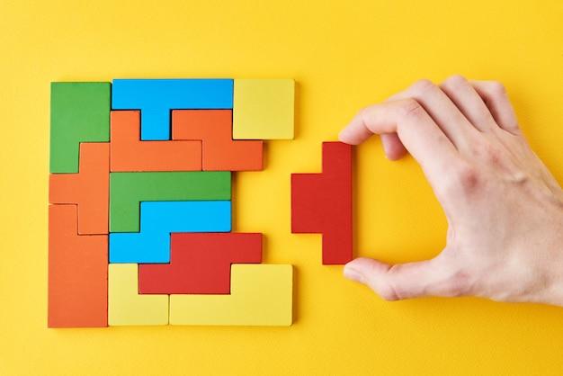 Pensiero logico e concetto di compito di finitura. mano della donna che aggiunge l'ultimo blocco di legno mancante per finire un puzzle