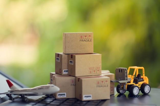 Concetto di trasporto merci e logistica il carrello elevatore a forche sposta una scatola di carta sulla tastiera del notebook