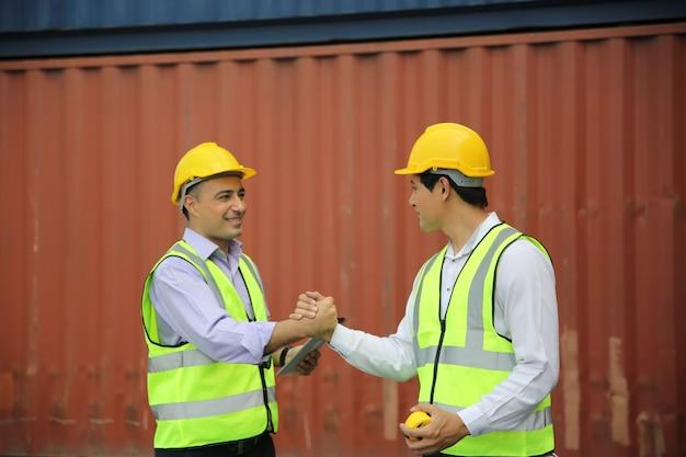 Controllo dell'ingegnere logistico al porto, carico di container per l'esportazione di camion e importazione del concetto logistico