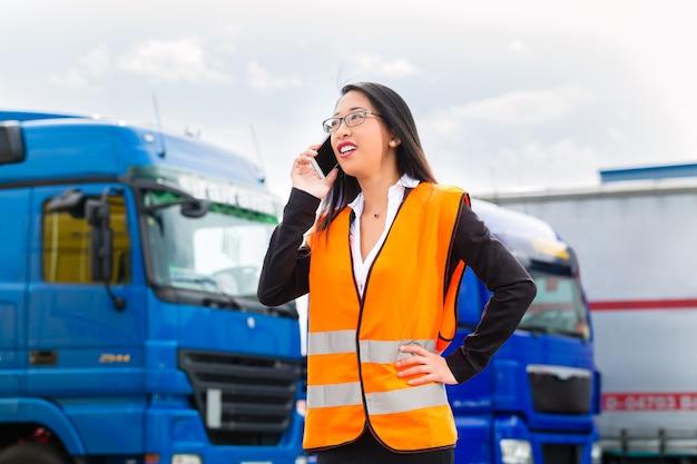 Logistica - spedizioniere o supervisore asiatico donna con telefono cellulare, davanti a camion e rimorchi, sul punto di trasbordo