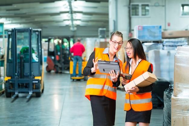 Logistica: operaia o spedizioniere e dipendente o collega, con giubbotto protettivo e scanner, scansiona il codice a barre del pacco, si trova al magazzino della società di spedizioni