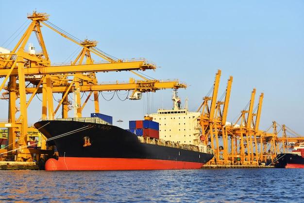 Logistica e trasporto della nave da carico del contenitore con il ponte della gru funzionante in cantiere navale alla sera