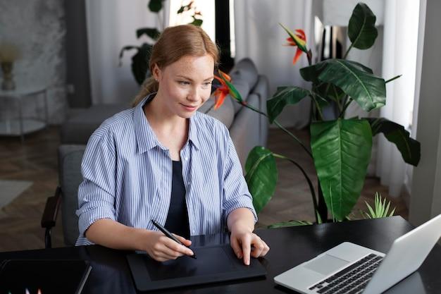 Logo designer che lavora sul suo tablet collegato a un laptop