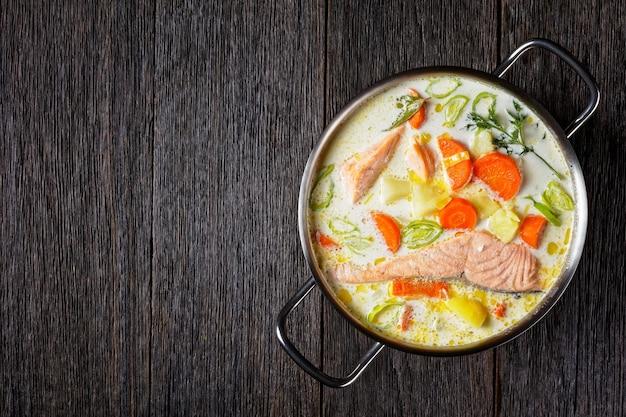Lohikeitto, zuppa di salmone con panna, patate, carote, porro e aneto in una pentola su un tavolo di legno scuro, cucina finlandese, piatto classico, vista orizzontale dall'alto, piatto, spazio libero