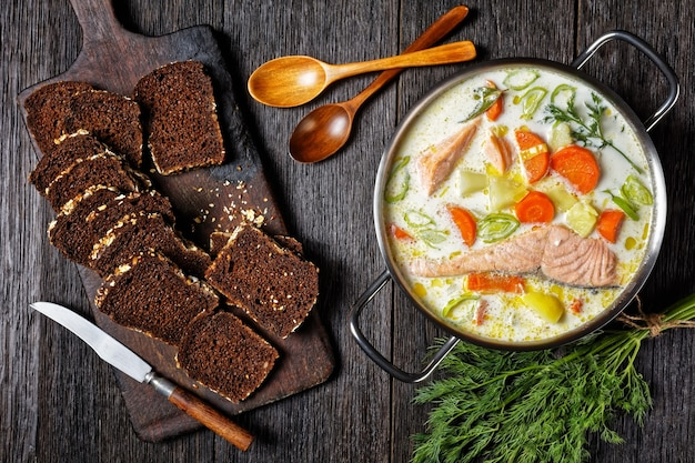 Lohikeitto, zuppa di salmone con panna, patate, carote, porri e aneto in una pentola su un tavolo di legno scuro con pane di segale, cucina finlandese, piatto classico, vista orizzontale dall'alto, piatto