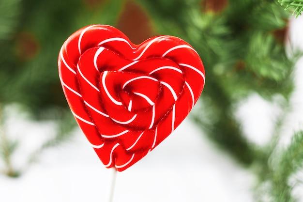 Caramella lecca-lecca sotto forma di un cuore bianco rosso isolato su un concetto di giorno di biglietti di s. valentino del bokeh vago