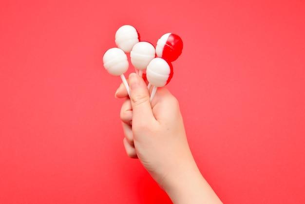 Lecca-lecca in mano femminile su sfondo rosso. spazio per testo o design.