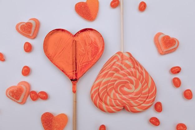 Lecca lecca, marmellata. caramelle gommose a forma di cuori su uno sfondo bianco. san valentino