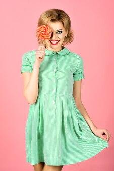 Lecca lecca. cibo dolce, dessert, zucchero. bellissima modella pin up con lecca-lecca in mano. ragazza di moda retrò divertente sexy in abito estivo con caramelle colorate. copia spazio per pubblicizzare.
