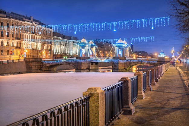Ponte lomonosov sul fiume fontanka a san pietroburgo e decorazioni di capodanno alla luce di una notte invernale blu