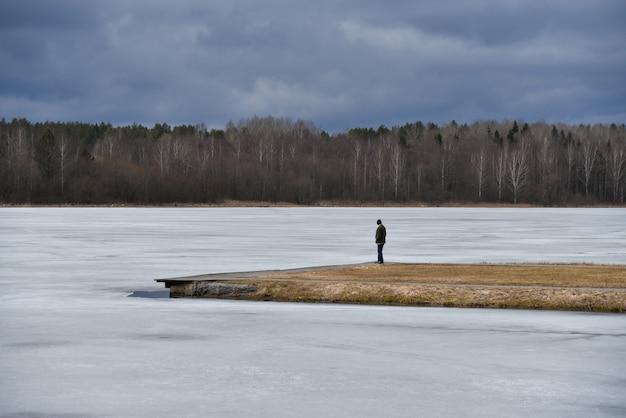 Un uomo solitario sull'isola guarda il lago ghiacciato