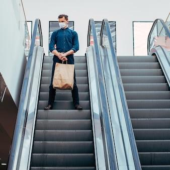 Uomo solo con una maschera protettiva in piedi sui gradini della scala mobile. foto con copia-spazio Foto Premium