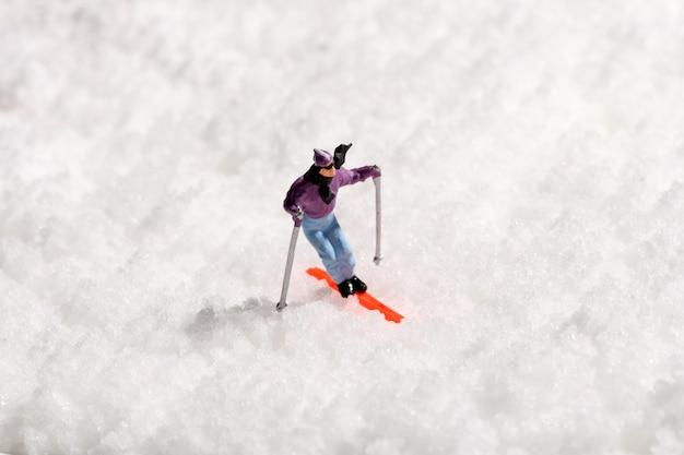 Uomo in miniatura solitario sciare sulla neve fresca d'inverno