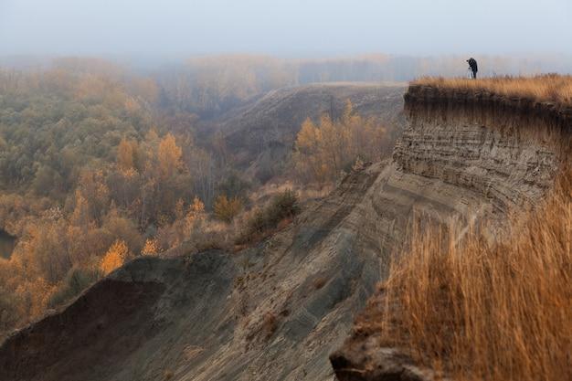 Un fotografo solitario sull'orlo di una scogliera