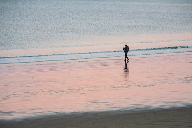 Un turista solitario con uno zaino riprende un meraviglioso paesaggio artico al tramonto sull'oceano