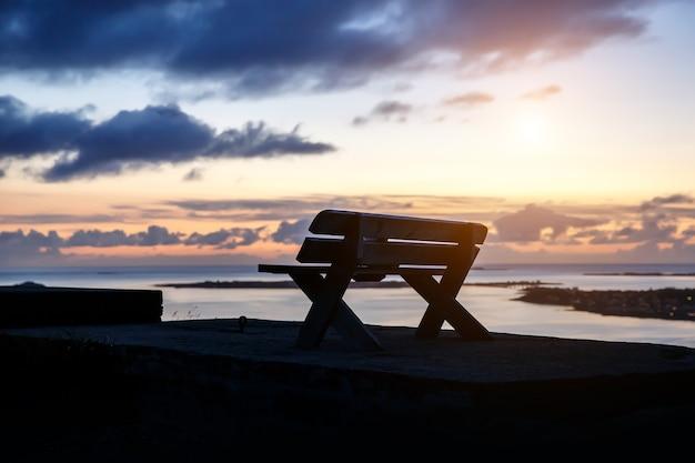 Una panchina di legno solitaria si trova in cima a una montagna. serata al tramonto