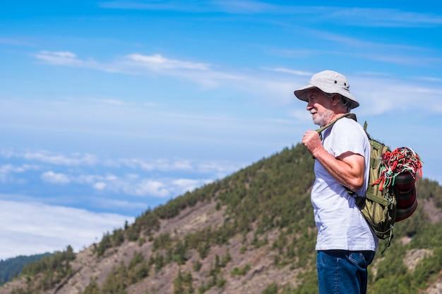 Trekker di età adulta solitario con zaino in piedi e guardando il bellissimo paesaggio in montagna - trekking ed escursionismo per persone mature in attività ricreative all'aperto