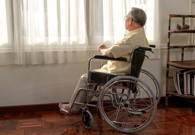 L'uomo anziano asiatico solitario era malato e seduto su una sedia a rotelle. stile di vita in età pensionabile e stare a casa da soli.
