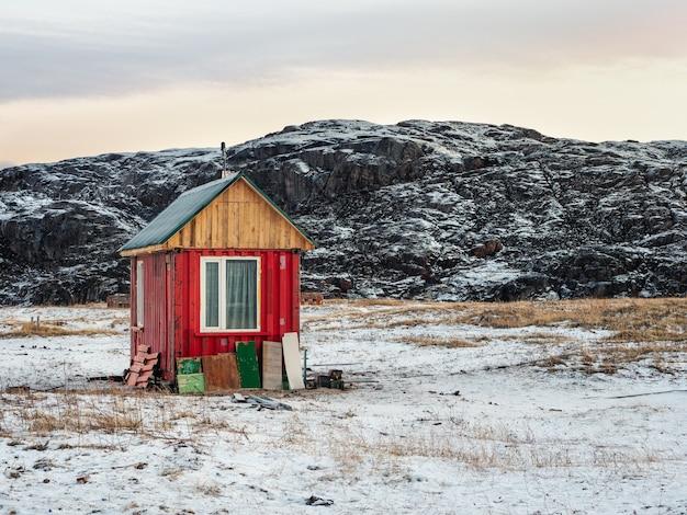 Una solitaria casa rossa autentica nella tundra artica in inverno.