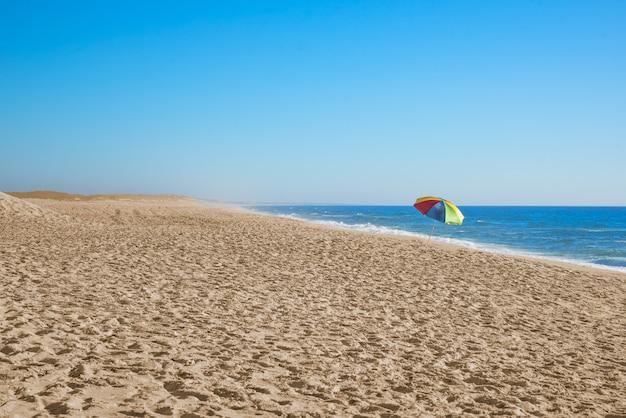 Spiaggia solitaria con ombrellone in lontananza
