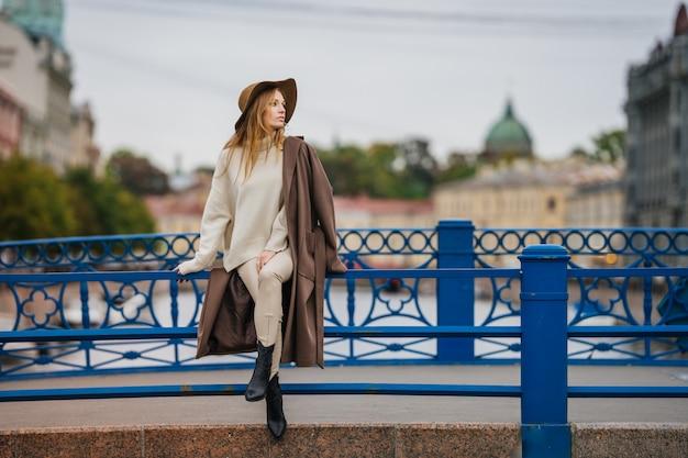 La bella giovane donna alla moda rossa sola si è vestita in un cappotto beige