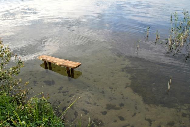 Panchina solitaria in piedi nell'acqua del lago