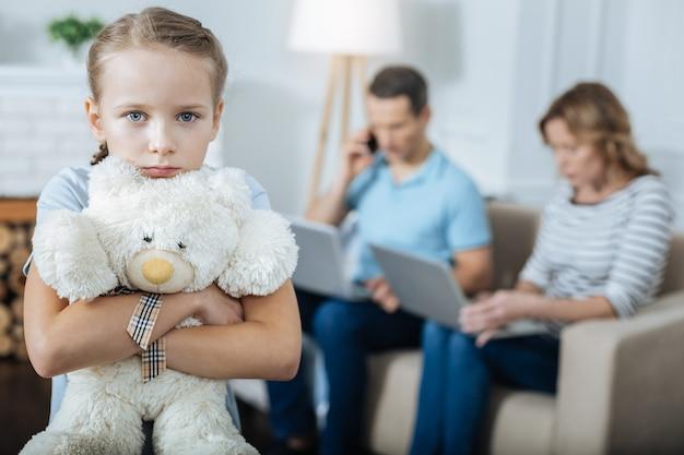 Bambina bionda sola dagli occhi azzurri in piedi e tenendo il suo giocattolo ei suoi genitori che lavorano in background