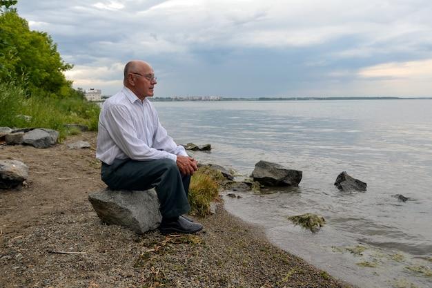 Un uomo anziano solo si siede su una roccia vicino al lago e guarda in lontananza