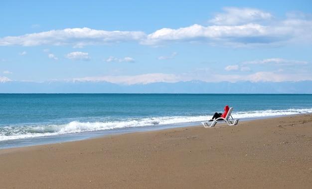 Turista femminile solitario in giacca rossa e pantaloni neri si siede sul lettino bianco sulla spiaggia sabbiosa e guardando le onde del mare e le alte montagne con cappucci di neve lontano in bassa stagione