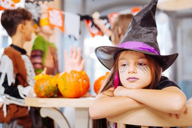 Ragazza solitaria. bella ragazza dai capelli scuri con labbra viola che indossa il costume di halloween del mago sentendosi sola