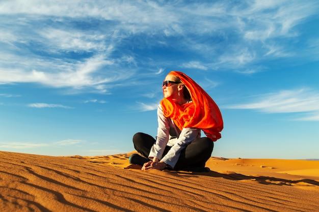 Ragazza sola nel deserto del sahara al tramonto. erg chebbi, merzouga, marocco.
