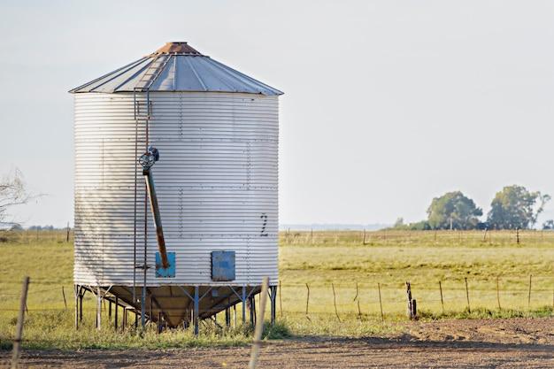 Silo solitario di stoccaggio del grano sul lato di una recinzione in un campo