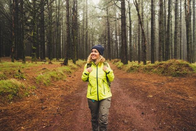 Donna felice sola che cammina in una foresta nebbiosa